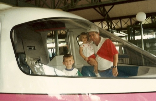 Father holding toddler girl with young boy in front of monorail at Walt Disney World