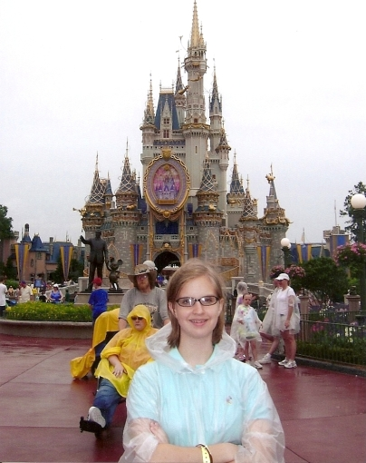 Teenage girl wearing rain poncho standing in front of Cinderella's Castle