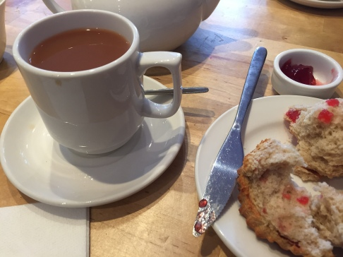 Cup of tea, scone with red jam
