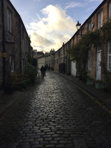 Curved street of cobblestone with quaint homes