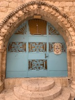 Teal colored door in stone wall