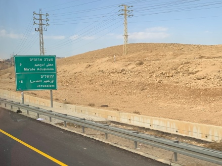 Highway next to brown, rocky hills with sign to Jerusalem