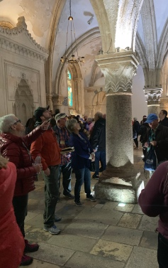 Tour guide talking to people in a room with vaulted ceiling and columns