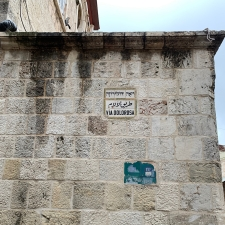 Tile Sign in block wall that reads Via Dolorosa