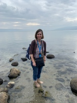 Woman standing in clear, ankle-deep water at the shoreline of the Sea of Galilee
