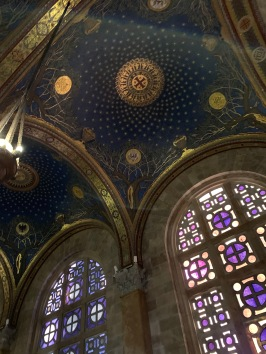 Blue domed ceiling of church with stars, stained glass window on side