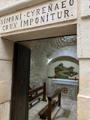 small chapel with kneeling benches and an image of Simon of Cyrene taking the cross from Jesus