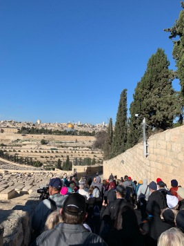 People walking down a road from the Mount of Olives toward the Kidron Valley