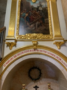 Chapel with a painting of Jesus falling under the weight of the cross. A crown of thorns is below the painting.