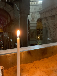 Single candle burning in church