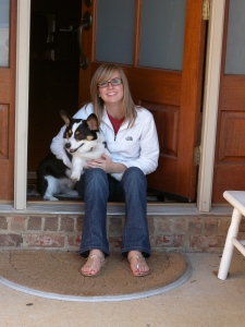 Teen girl in jeans and white fleece shirt holding black, white and tan corgi