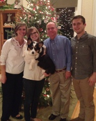 Mom, college aged daughter holding a black, white and tan corgi, dad and college aged son standing in front of a Christmas tree