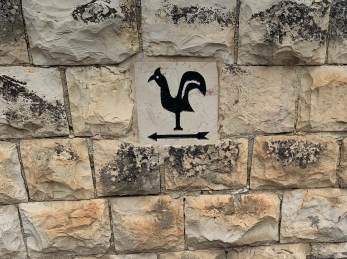 simple painting of a rooster on a stone wall