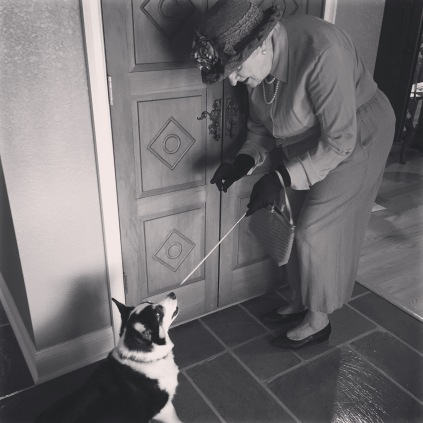 Black and white photo of a woman pretending to be the queen pointing a sword toward a black and white corgi