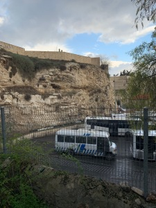 Buses parked next to a rocky cliff