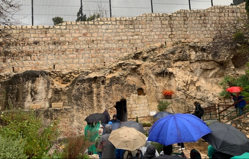 People with umbrellas walking down steps towards an empty tomb in a rocky wall.