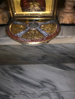 Gold disc on white marble floor that covers the stone of Golgotha