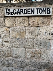 Sign on rock wall that reads to the Garden Tomb