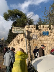 People on sidewalk under a sign pointing the way to the Garden Tomb