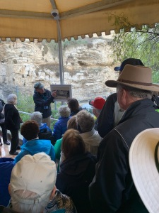Tour guide pointing out something on old photograph in front of a rocky cliff