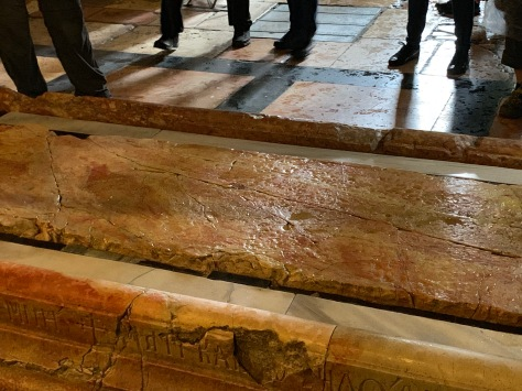 Brown, stone slab about six feet long lying on floor of church