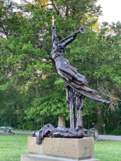 Bronze modern statue of an angel with a trumpet taking flight over a fallen soldier