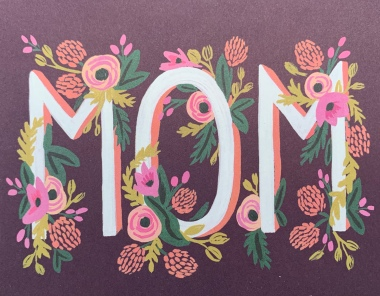 Purple card with MOM written in white letters which are surrounded by flowers