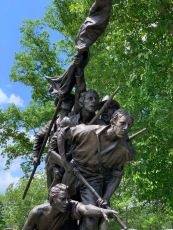Bronze statue of 5 men heading into battle, one holding a flag, three holding rifles and one kneeling and pointing.