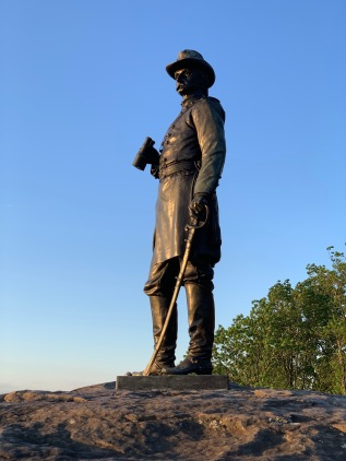 Bronze statue of a Union Soldier standing on top of a rock, a sword in his left hand and a pair of binoculars in his right