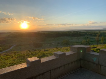 View of a field, some trees and a sunset from a tower on a hill