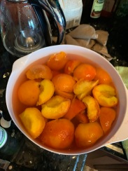 peach halves in a bowl of water