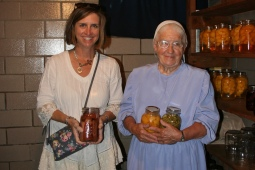 Woman with Mennonite woman holding jars of fruit
