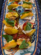 Tray with sliced peaches, tomatoes and mozzarella cheese